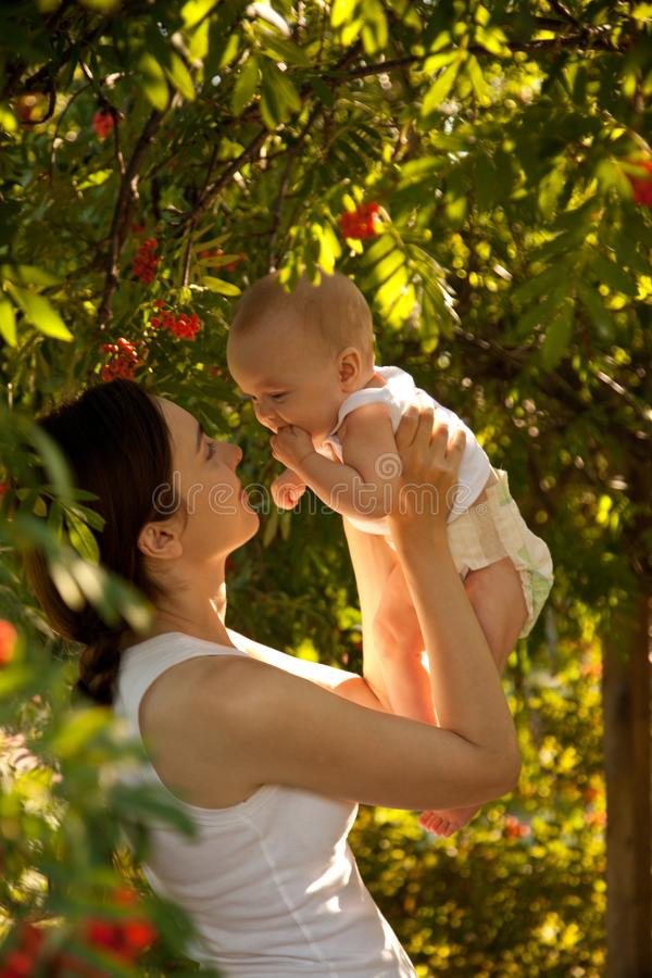 Free Happy Woman Holding In Arm A Baby In A Garden. Happy Family. Royalty Free Stock Photography - 118175047