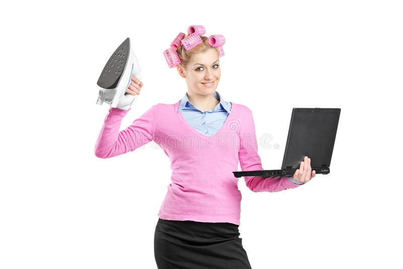 Happy woman holding a laptop and an iron. Isolated on white background stock images