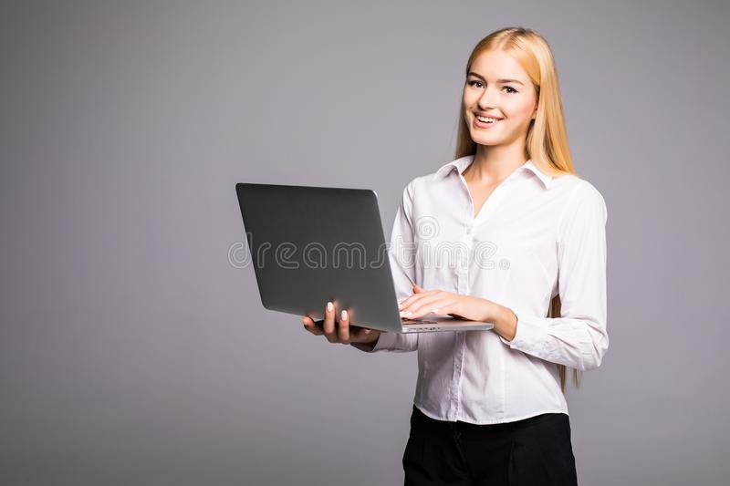 Happy woman holding laptop and looking at camera over gray background. Happy young woman holding laptop and looking at camera over gray background stock photos