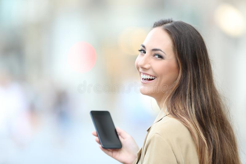 Happy woman holding phone looks at camera in the street stock photography