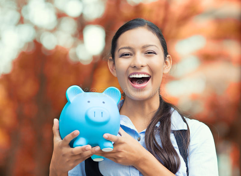 Happy woman holding piggy bank. Closeup portrait happy, smiling business woman, bank employee holding piggy bank, isolated outdoors indian autumn background royalty free stock photos