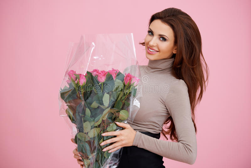 Happy woman holding pink roses royalty free stock images