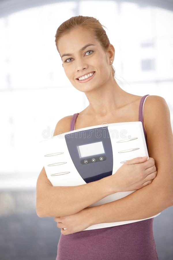 Happy Woman Holding Scale In Arms Royalty Free Stock Photo