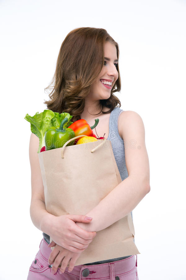 Happy woman holding a shopping bag full of groceries stock photo