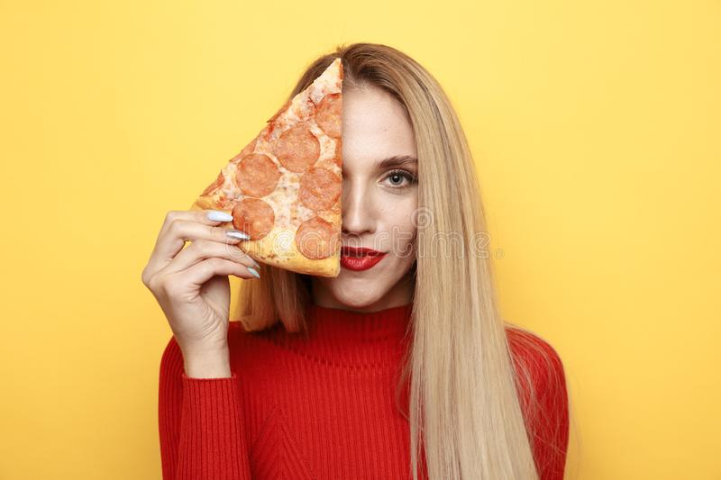 Happy woman holding tasty slice of pizza for lunch in the yellow studio. royalty free stock photos