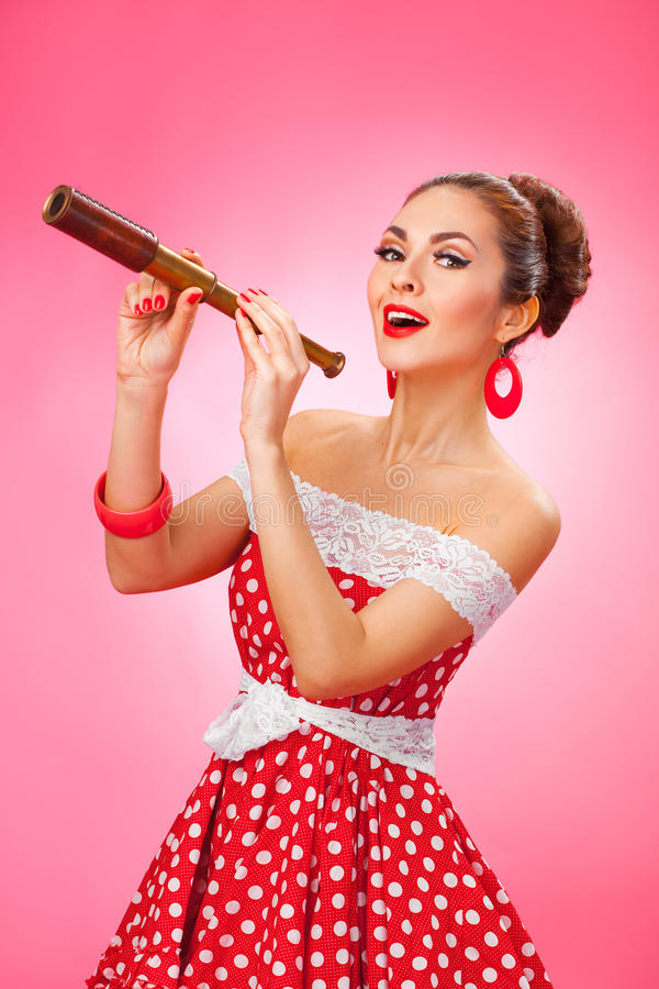 Happy Woman Holding Telescope. Pin-Up Retro style. Portrait of a smiling young female model with hand-held telescope in her arms wearing red dress royalty free stock image