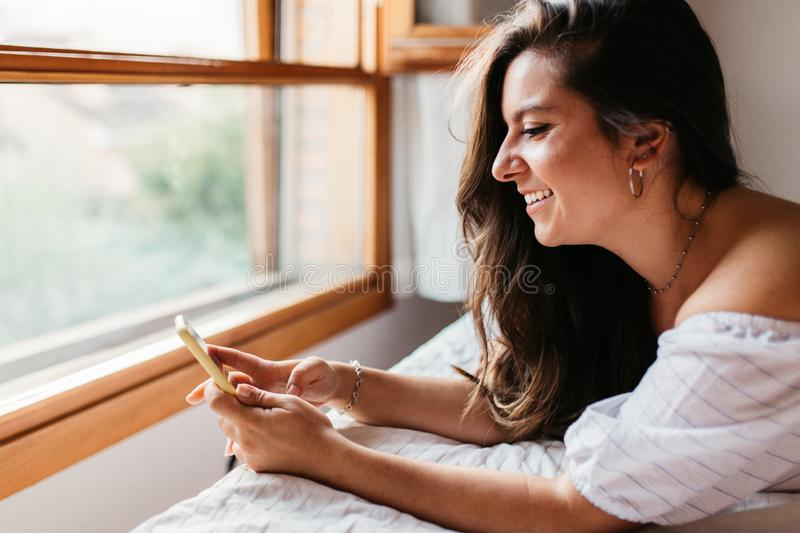 Happy woman at home texting in her mobile phone in bright bedroom. Checking social apps with smartphone. Lifestyle concept stock image
