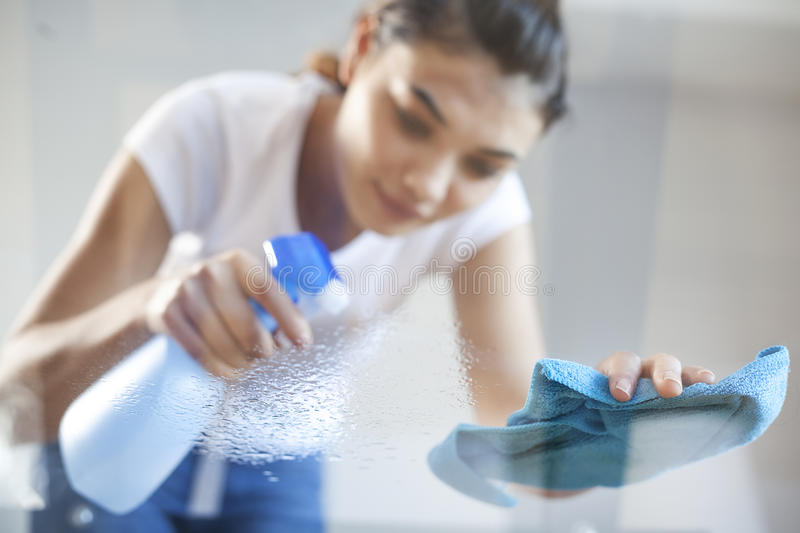 Happy woman house wife cleaning glass table in home royalty free stock photos