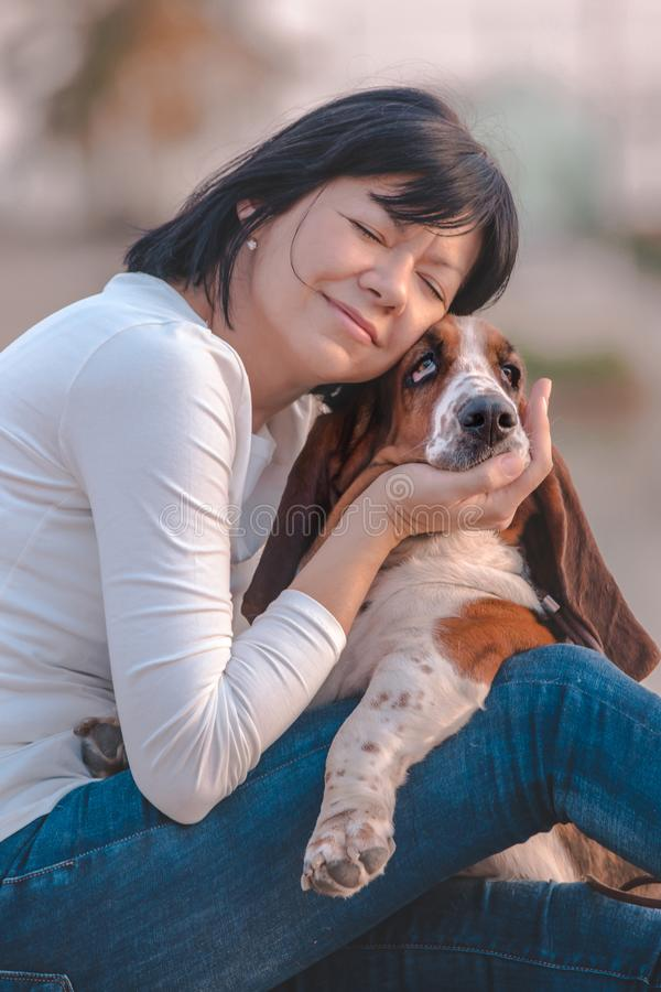 Happy woman hugging her dog Basset Hound royalty free stock photography