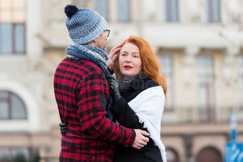 Happy woman hugs man in hat on the street. Happy couple hugging on the city background. Sensual brunette woman stock image
