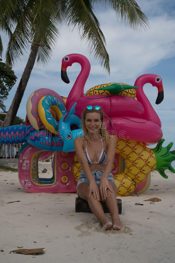 Happy woman with inflatable toys on the beach. Smiling happy woman with bunch of many colorful inflatable toys isolated on the sandy tropical beach over blue sky royalty free stock photography