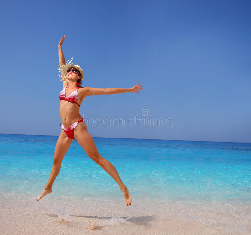Happy Woman jumping on the beach royalty free stock image
