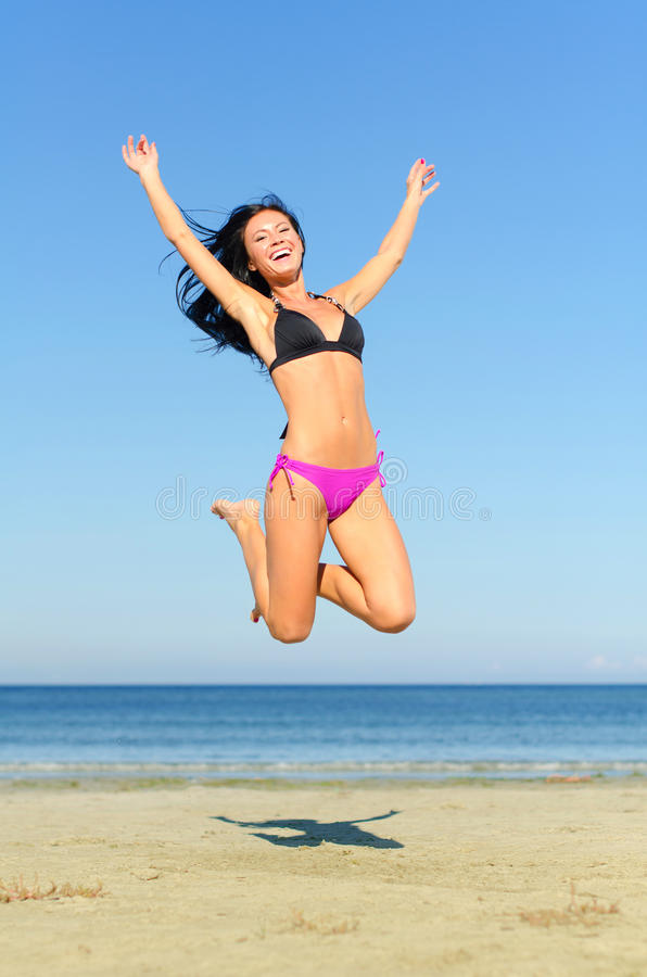 Happy woman jumping. At the beach stock image