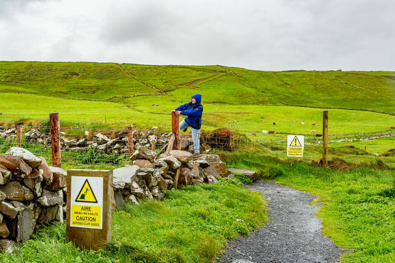 Happy woman jumping a fence on a rainy day in the coastal walk route from Doolin to the Cliffs of Moher. Geosites and geopark, Wild Atlantic Way, spring day in stock images