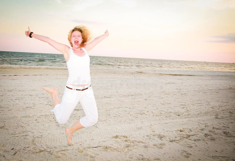 Happy Woman Jumping for Joy. A happy woman jumping at the beach royalty free stock photos