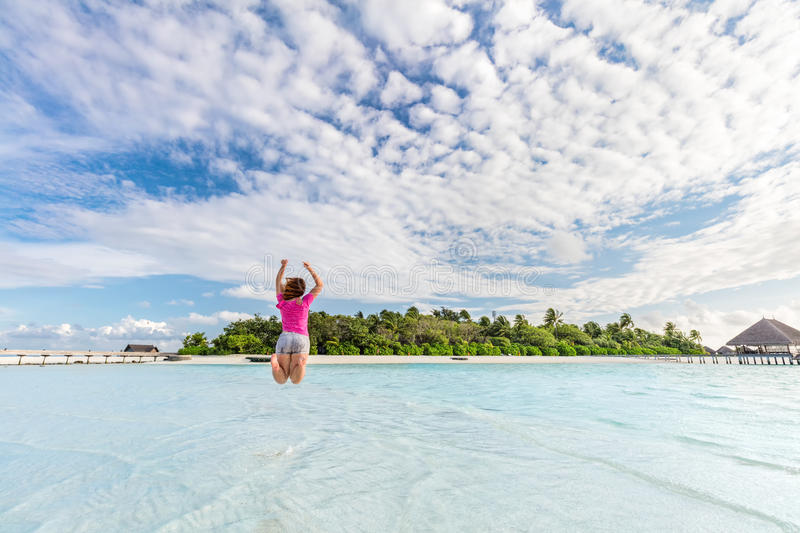 Happy woman jumping for joy in ocean on tropical island in Maldives royalty free stock images