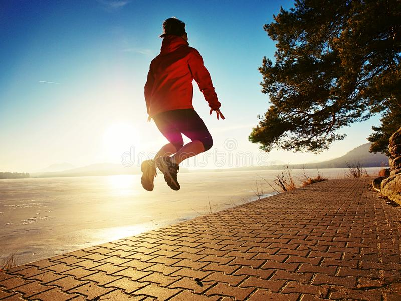 Happy woman jumping on lake shore, path beach at sunset stock photography