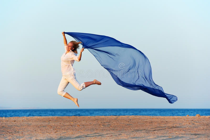 Happy woman jumping on sea beach. With blue flying silk cloth royalty free stock photography