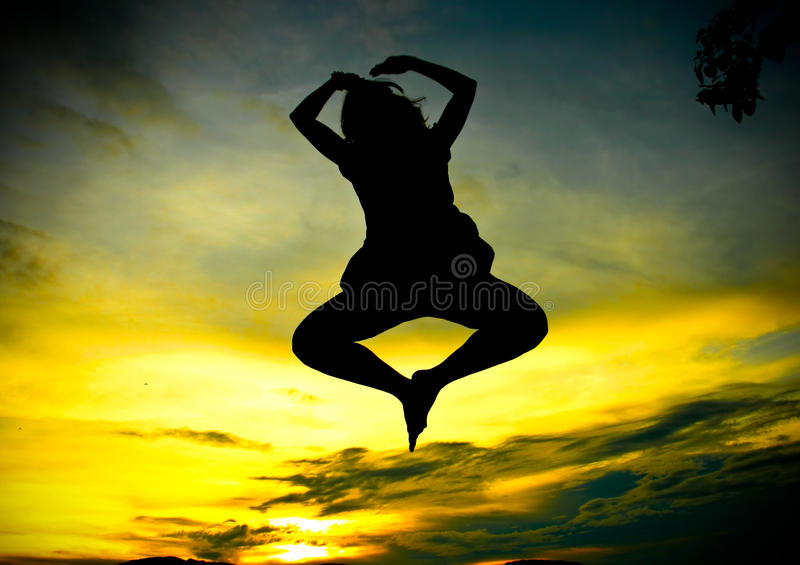 A happy woman jumping at sunset. Silhoutte stock photography