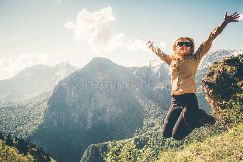 Happy Woman jumping up raised hands mountains royalty free stock photos