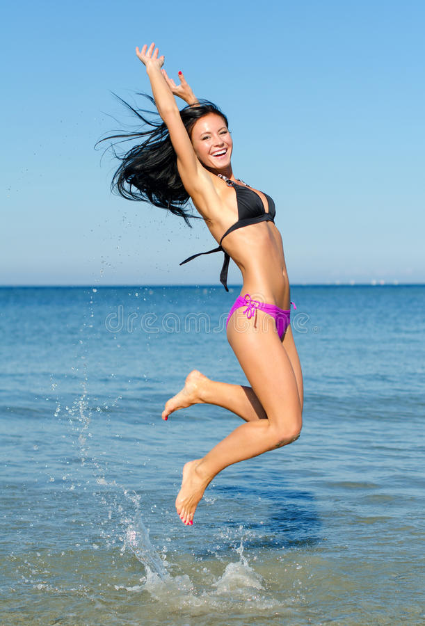 Happy woman jumping. In the water at the beach royalty free stock photography