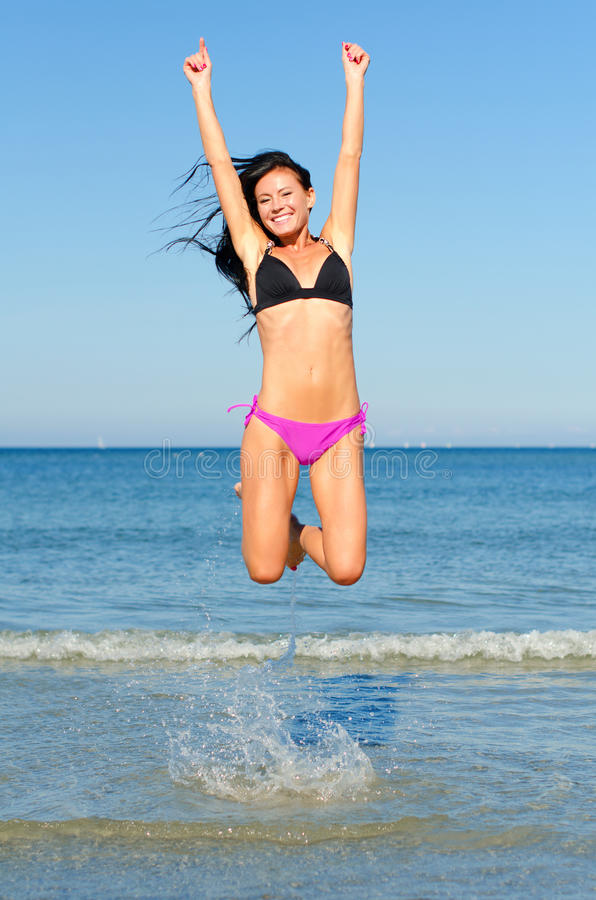 Happy woman jumping. In the water at the beach stock photos