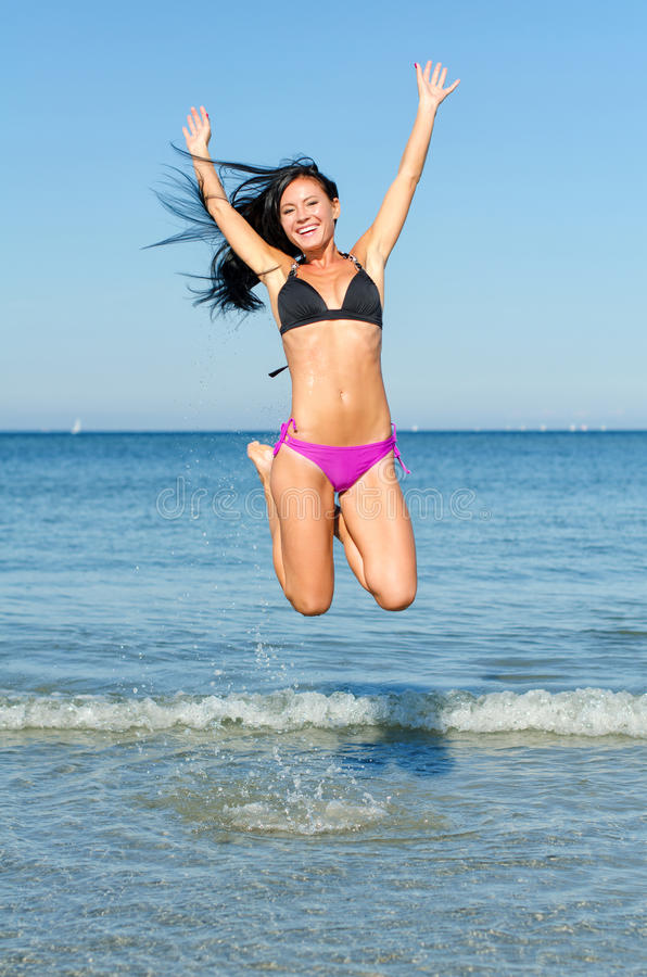 Happy woman jumping. In the water at the beach stock image