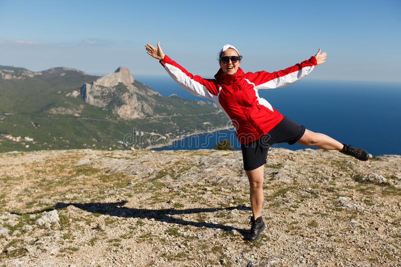 Happy woman jumps on a peak of a mountain in summer time in mountains enjoying the climb with beautiful rocky and sea royalty free stock image