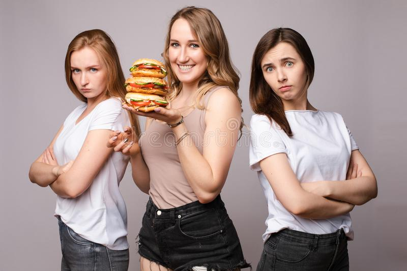 Happy woman keeping burger while sad girls standing near royalty free stock photography