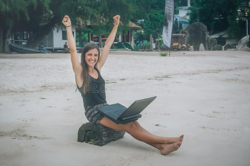 Happy woman with laptop enjoying in swing on tropical beach. Koh Tao, Thailand royalty free stock images