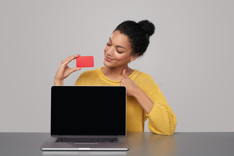 Happy woman with laptop holding blank credit card. Smiling mixed race african american - caucasian woman showing blank black laptop computer screen and blank royalty free stock images