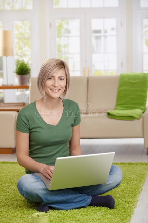 Happy woman with laptop at home. Happy woman sitting on floor at home in living room using laptop computer, looking at camera stock photo
