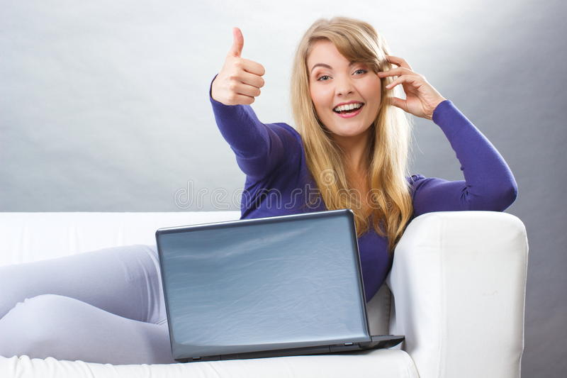 Happy woman with laptop sitting on sofa and showing thumbs up, modern technology. Happy smiling woman with laptop sitting on sofa and showing thumbs up, typing royalty free stock image