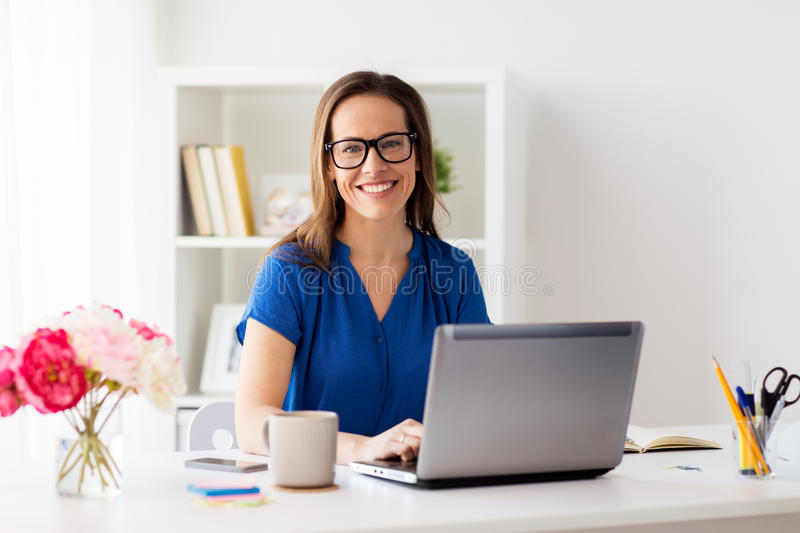Happy woman with laptop working at home or office royalty free stock photography