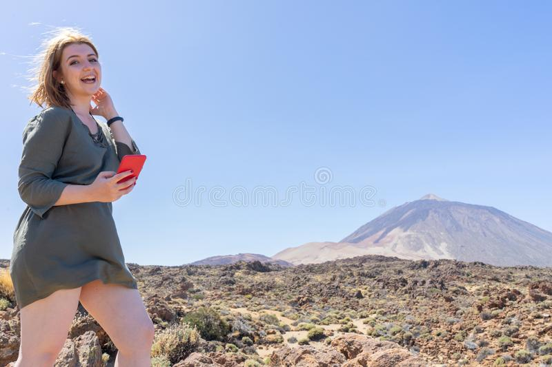 Happy woman laughing, reading a message from social media in her smart phone in a desert spot in the famous volcano El Teide, in. Tenerife. Caucasian blonde stock images
