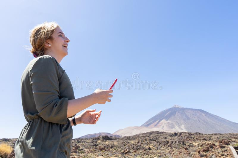 Happy woman laughing, reading a message from social media in her smart phone in a desert spot in the famous volcano El Teide, in. Tenerife. Caucasian blonde royalty free stock photos