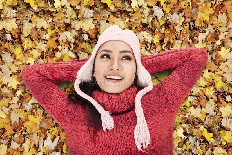 Happy woman laying on Autumn leaves. Happy Asian woman laying on Autumn leaves in the park stock images
