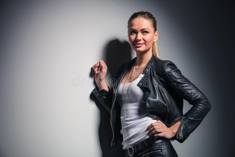 Happy woman in leather clothes looks to side stock photos