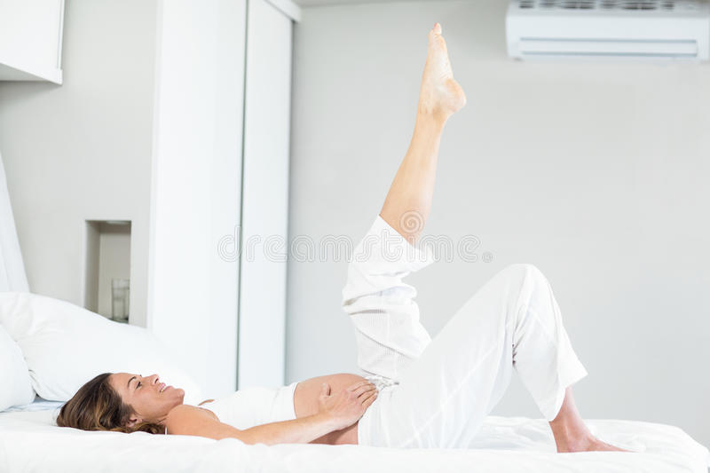Happy woman with leg up on bed royalty free stock photo