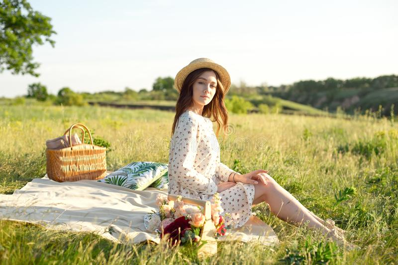 Happy Woman Life Style, beautiful relaxed girl in a straw hat on the nature picnic basket flowers in the rays of the stock photos