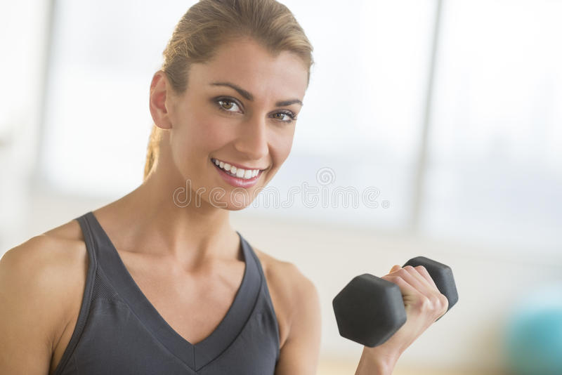 Happy Woman Lifting Weights At Health Club. Portrait of happy young woman lifting weights at health club stock photo