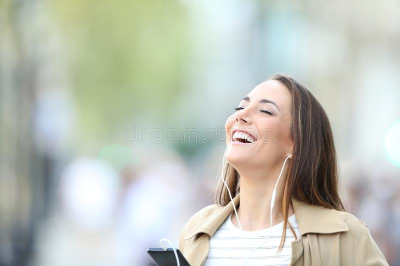 Happy woman listening to music breathing in the street royalty free stock image