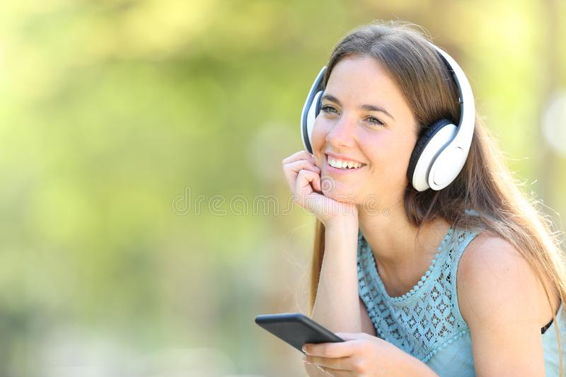 Happy woman listening to music looking away. Happy woman listening to music holding smart phone looking away in a park with a green background royalty free stock images