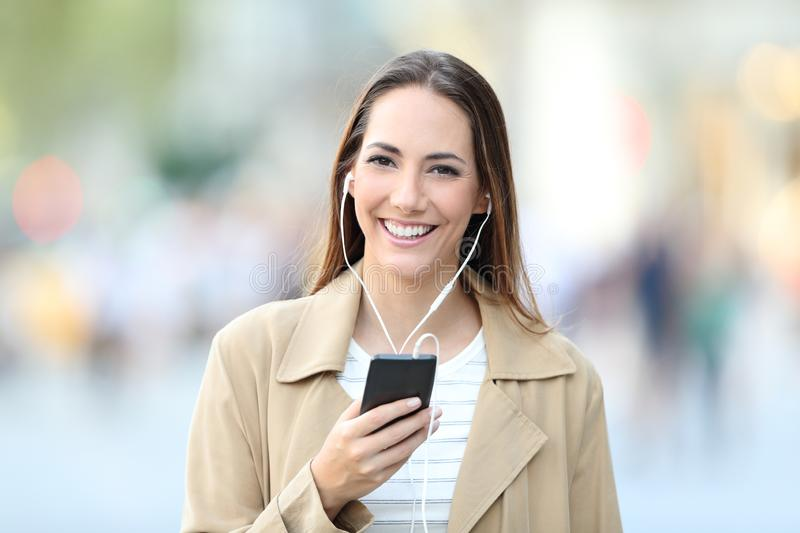 Happy woman listening to music looks at camera royalty free stock photos