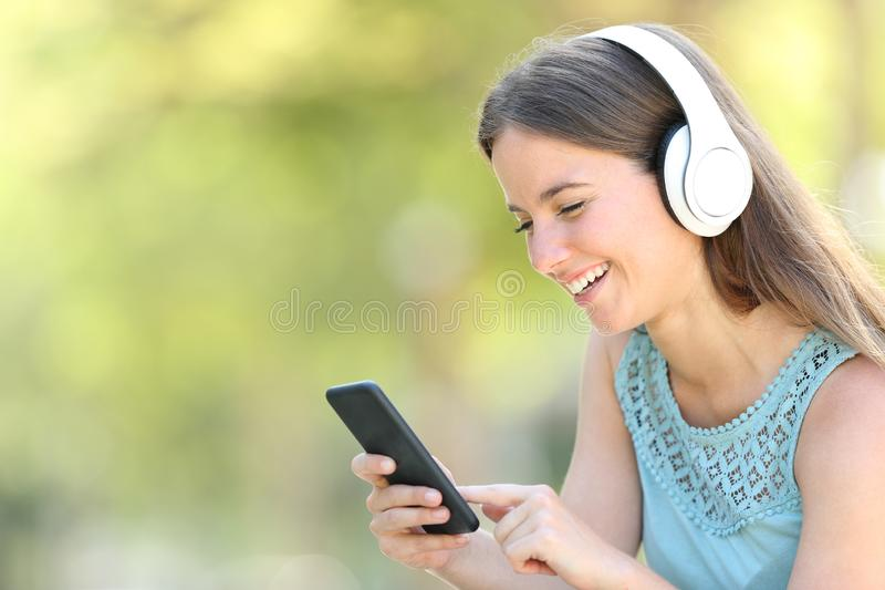 Happy woman is listening to music using smart phone. In a park with a green background royalty free stock photo