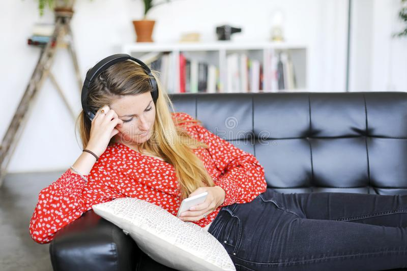 Happy woman listening to music wearing headphones using a smartphone sitting on a sofa stock image