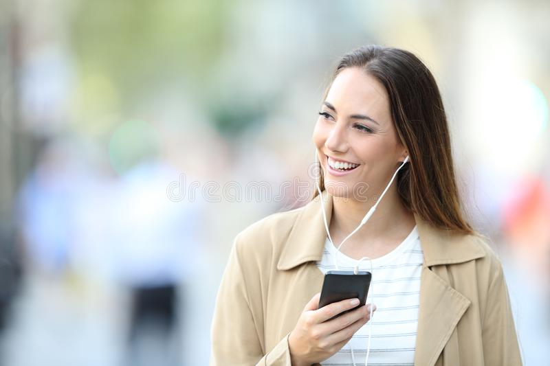 Happy woman listens to music looking at side royalty free stock photos