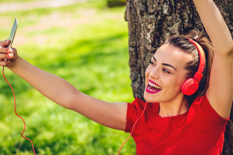 Happy woman listens to music via headphones and smartphone outdoor royalty free stock image