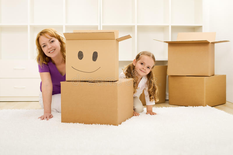 Happy woman and little girl unpacking. And having fun in a new home royalty free stock images