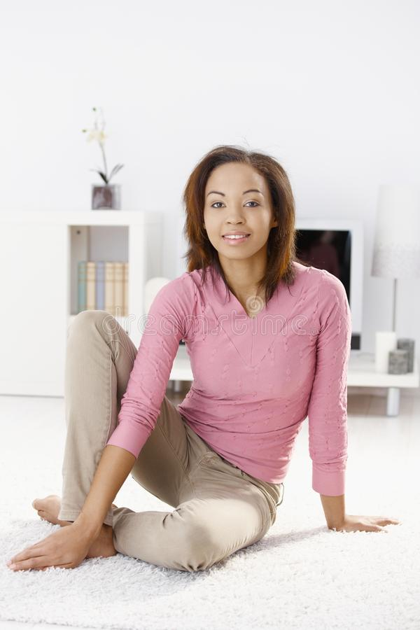 Happy woman in living room. Happy woman sitting on living room floor, smiling at camera stock images